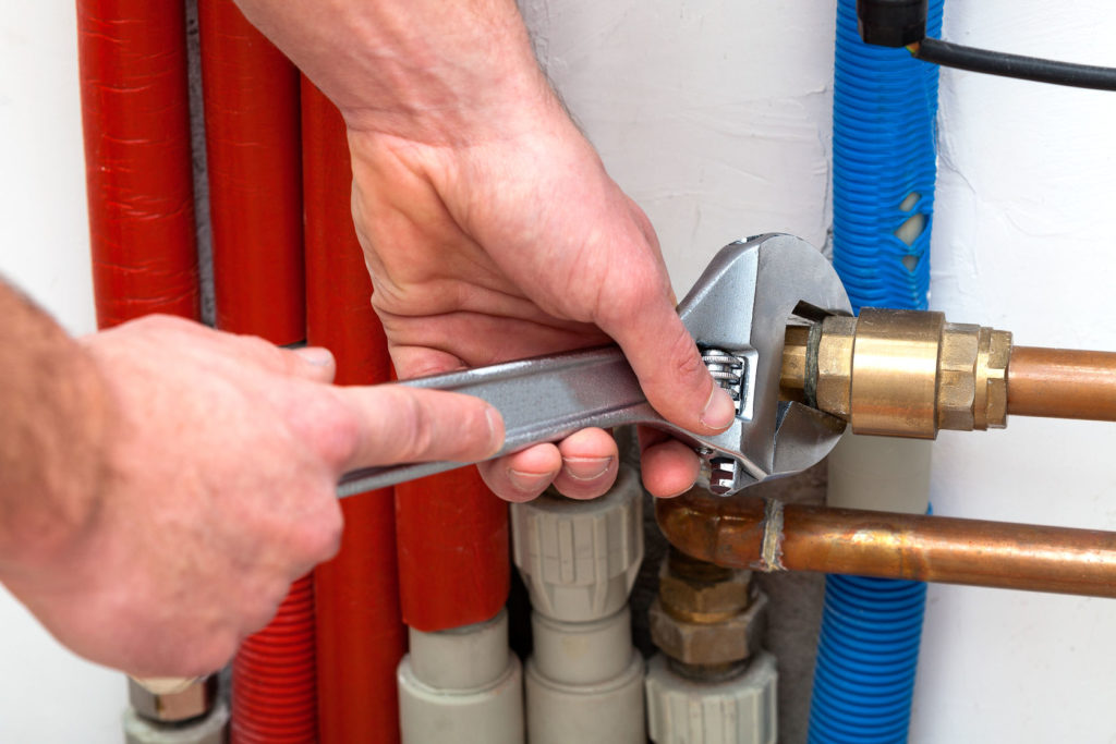 Man's hands with wrench turning off valves